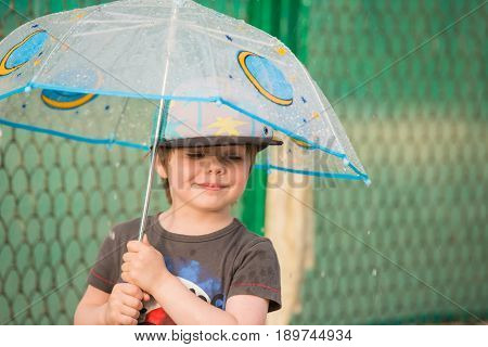 Smiling boy holding an umbrella under the rain