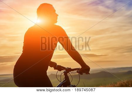 Close-up of silhouette of cyclist standing with bike against beautiful sunset. Sportsman in the sportwear. Extreme travelling in the countryside. Beautiful landscape. Concept of the healthy and active lifestyle.