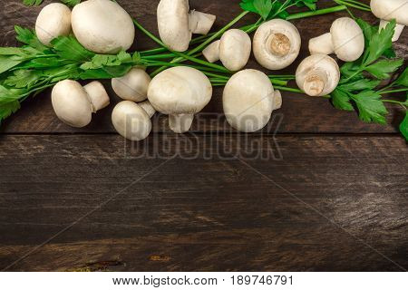 An overhead photo of fresh white mushrooms with green parsley, on a dark rustic texture with a place for text