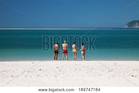 Group of adult people stay on the beach in Troia, Setubal, Portugal
