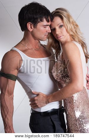 The attractive couple is in a loving enchanting embrace.