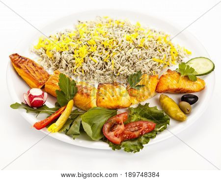 Studio closeup shot of a grilled salmon kebab with rice and herbs on a plain plate on white background. Healthy dietary concept with essential nutrients and long-chain polyunsaturated fatty acids.