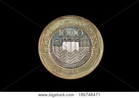 A close up image of a 1000 colombian peso coin on a black background