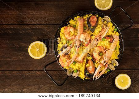 A photo of a Spanish seafood paella in a typical paellera, with mussels, clams, shrimps, and lemon wedges, shot from above on a dark rustic texture with a place for text