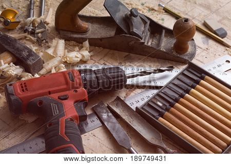 Various Tools For Carpentry On The Table. Screwdriver, Ruler, Chisel On A Wooden Surface.