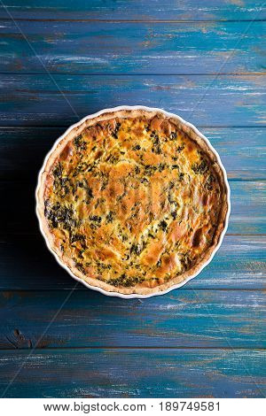 Homemade spinach french pie quiche lorraine on wooden board with place foe text