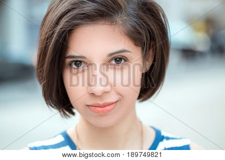 Closeup portrait of beautiful smiling young latin hispanic girl woman with short dark black hair bob outside looking in camera natural smile emotion ethnic diversity