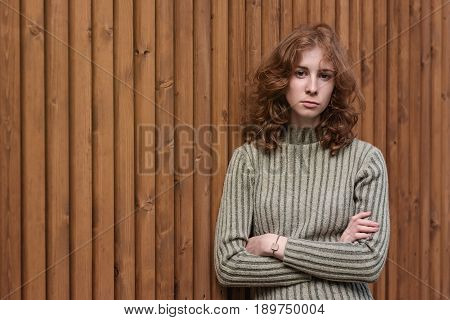 A beautiful red-haired girl in a green sweater is standing by the wooden wall. She crosses her arms and looks severely at the camera.
