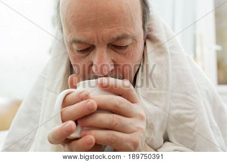 The elderly man covered himself with a blanket and holds a mug in his hands. Self-medication at home.