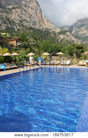 30TH MAY 2017, KABAK, TURKEY : English tourists having a swim and cooling off in an infinity pool at the olive garden in Kabak in Turkey, 30th may 2017