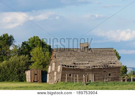The dilapidated barn with caved in roof from the side. Barn is set in a green meadow with deciduous trees and cloudy sky above.