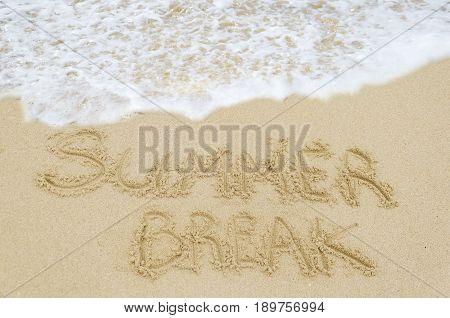 Sign Summer Break on the sandy beach near ocean