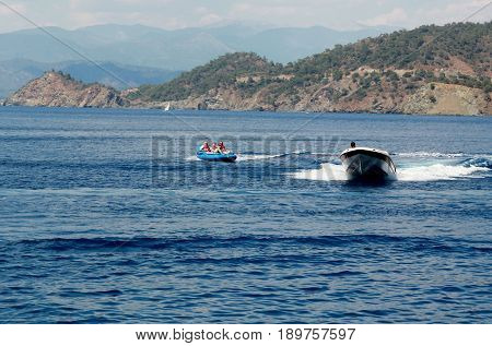 FETHIYE, TURKEY 1ST JUNE 2017: Tourists having fun riding in inflatables being pulled by a speedboat in a bay at Fethiye ,Turkey, 1st june  2017
