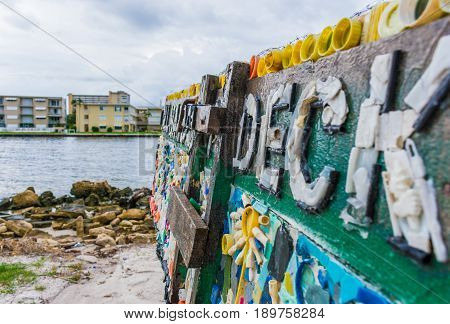 Close up of Cuban refugee raft upcycled into art by using local beach garbage to decorate. On display at a beach park on the intracostal waterway