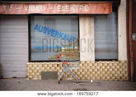 An empty shopping cart is standing on the sidewalk in front of a shop with an open window closed for business.