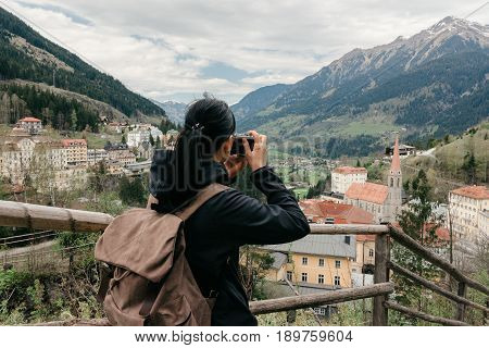 BAD GASTEIN, AUSTRIA - 22 APRIL 2016: Girl traveler with a retro camera and a backpack is on the observation deck with a view of the Alpine village and mountains