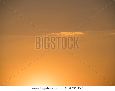 golden sky with one lonely cloud at sundown