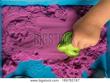 Child hand stamping turtle shaped mould in colorful kinetic sand