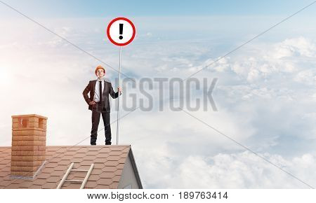Young businessman with roadsign in hand standing on brick roof. Mixed media