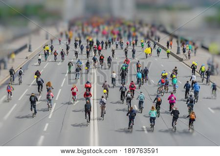 Parade of bicyclists in city center. Mass urban cycling marathon. Youth and families with children ride bicycles. Concept of healthy lifestyle. Copy space. Selective focus. Effect of the tilt shift