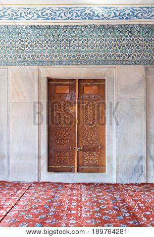 Istanbul, Turkey - April 16, 2017: Wooden aged engraved door marble wall and ceramic tiles with floral blue decorative patterns Sultan Ahmet Mosque (Blue Mosque) Istanbul Turkey