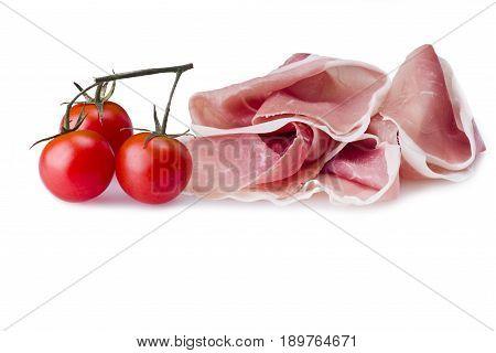 Raw ham leg sliced with three tomatoes
