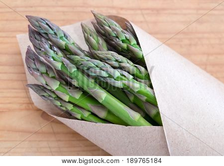 Green asparagus vegetables from a farmers market in brown paper packaging - landscape orientation