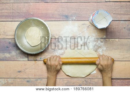 stretching dough with rolling pin on wooden table for cooking
