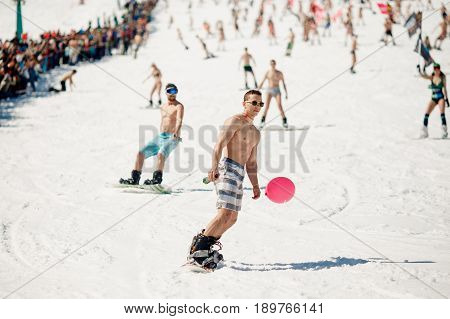 Sheregesh, Kemerovo region, Russia - April 16, 2016: Grelka Fest is a sports and entertainment activity for ski and snowboard riders in bikini. man goes down on a snowboard
