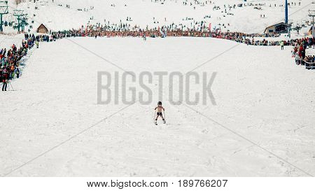 Sheregesh, Kemerovo region, Russia - April 16, 2016: Grelka Fest is a sports and entertainment activity for ski and snowboard riders in bikini.child descends from the mountain in shorts