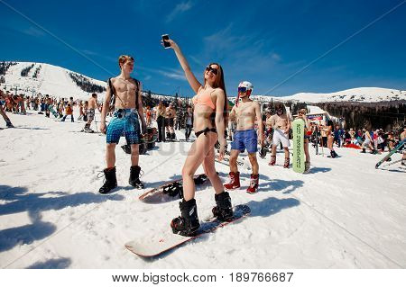 Sheregesh, Kemerovo region, Russia - April 16, 2016: Grelka Fest is a sports and entertainment activity for ski and snowboard riders in bikini.group of snowboarders friends in swimsuits.