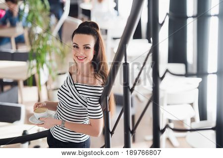 Confident team leader. Confident young woman holding a cup of hot coffee in her hands and looking at camera with smile while her colleagues working in the background