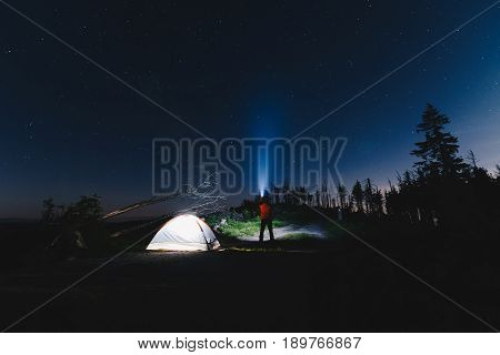 Tourist With Flashlight Near His Camp Tent At Night