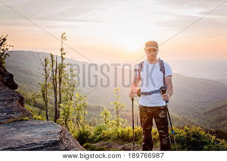 Man Tourist With Trekking Poles On Top Of Hill At Sunrise
