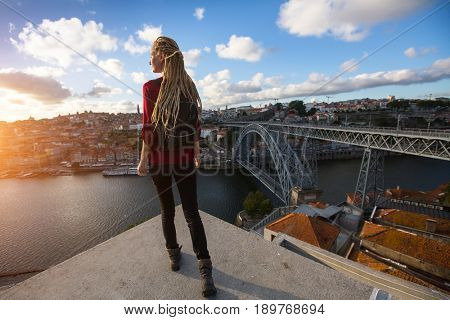 Young beautiful woman with blond dreadlocks meets sunset on the viewing platform opposite the Dom Luis I bridge across the Douro river in Porto, Portugal.