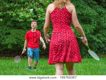Mother and son playing badminton in meadow with forest in background. Child with badminton rackets in hand. Kid have fun in summer park at day.