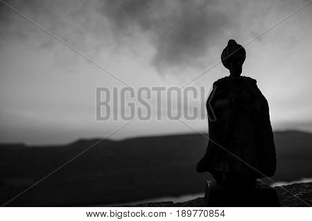 Silhouette Of Arab Man Stands Alone In The Desert And Watching The Sunset With Clouds Of Fog. Easter
