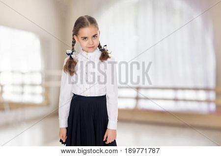 A beautiful little schoolgirl girl in a white blouse and black long skirt, with neatly braided pigtails on her head.She is standing right in front of the camera.Close-up.In the sports hall with mirror and a large semi-circular window.