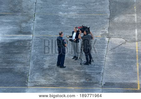 Auckland New Zealand - May 17 2017: Aerial view of a cameraman and woman reporter during a news interview. The work of photojournalism must be timely and relevant to contemporary news stories.
