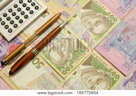 Two pens and a calculator lie on the banknotes of Ukrainian hryvnia.