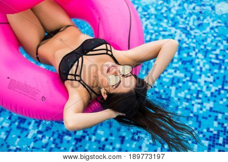 Sexy Woman In Bikini Enjoying Summer Sun And Tanning During Holidays In Pool With Cocktail. Top View