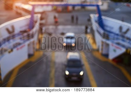 blurred shot of loading of cars on the ferry in sunset evening. Top view of ship bow