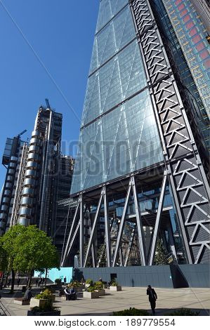London UK - May 13 2015: Business people have a lunch break outside 122 Leadenhall Street tower and Lloyd's building in City of London UK. Both designed by the awarded British architectural firm Rogers Stirk Harbour and Partners.