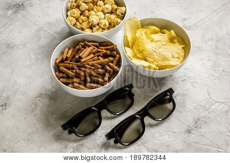 cinema and TV whatching with glasses, crumbs, chips and pop corn on stone background