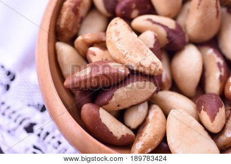 Close-up on a wooden bowl with Brazil nuts on white background