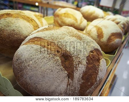 bread and buns in on shelf in bakery or baker's shop