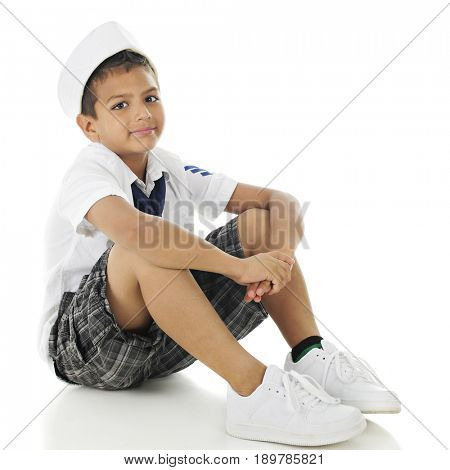 A handsome elementary boy casually sitting in his sailor hat, shirt and tie.  On a white background.