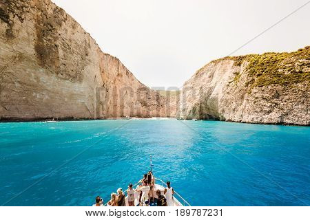 10 July 2016 Amazing landscape of Navagio beach with shipwreck on Zakynthos island cruise ship with people on deck approaching to the bay. Greece.