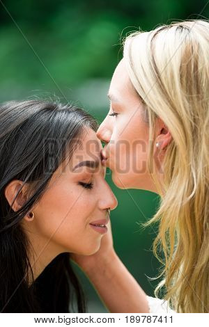 Close up of a lovely lesbian couple, blonde woman kissing in a forehead of a brunette girl, in a blurred background.