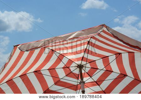 Red striped umbrella parasol to provide shade and sun protection against blue sky with light clouds